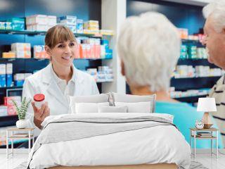 Chemist advising senior couple on a drug in her pharmacy
