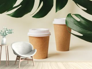 Disposable paper coffee cup and green leaf. Ecology concept