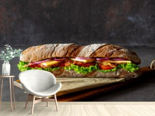 A sandwich of dark bread with salad, bacon, tomatoes, cheese and onions. Breakfast. Fast food.