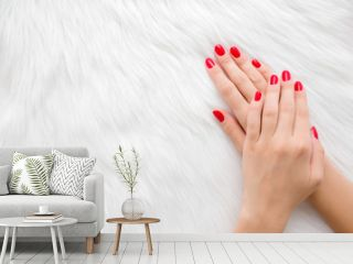 Beautiful groomed woman hands with red nails on light white furry background. Manicure, pedicure beauty salon concept. Empty place for text or logo. Closeup. Top down view.