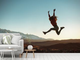 Happy girl jumps against mountains at sunset