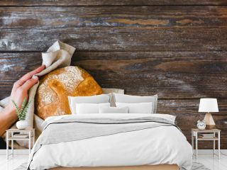 A woman holds in her hands a loaf of fresh baked homemade bread. Rustic wooden background rustic style. Horizontal frame