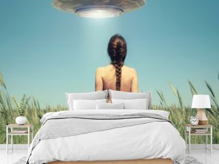A girl in the field watching a UFO in the sky. Fiction scene with alien spaceship. Photo with 3d rendering element