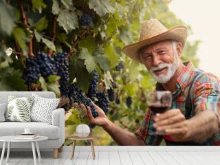 Winemaker in vineyard with glass of white wine