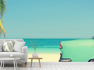 Classic car on a tropical beach with palm tree, panoramic vintage summer background