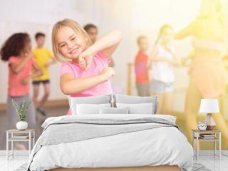 Smiling little girl training movements of vigorous dance with group of tweens in children dance studio