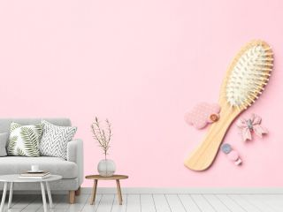 Flat lay composition with modern wooden hair brush on pink background. Space for text