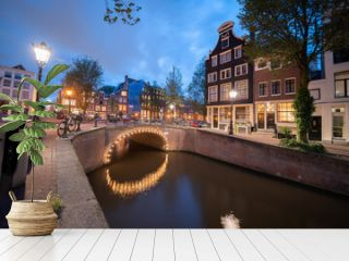 Amsterdam canal at night with stone bridge with arch illuminated and reflected in calm water