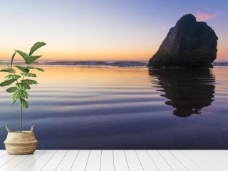 Beautiful seascape. Large rock in the ocean. Calm. The sun setting behind the horizon is reflected in orange rays in the calm water of the ocean. Postcard advertising tourist destinations.