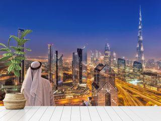 Arabian man watching night cityscape of Dubai with modern futuristic architecture in United Arab Emirates
