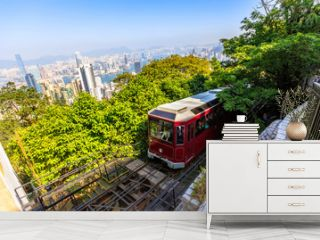 The popular red Peak Tram to Victoria Peak, the highest peak of Hong Kong island. Tourist tram with panoramic city skyline in the background in a sunny day.