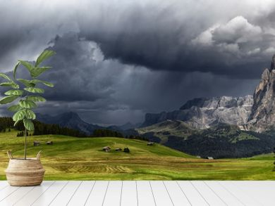 Storm over the mountains Dolomiti in the summer season with meadow in foreground