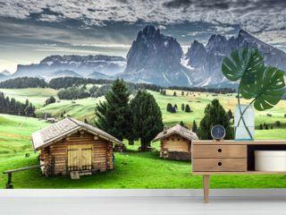 Small wooden huts at sunrise in Alpe di Siusi, Dolomites