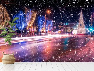 Night city with Christmas decorations, spruce and traces of headlights of moving cars, reflected in the wet road in a snowfall.