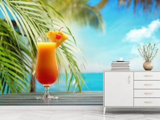 Refreshing orange cocktail on beach table.