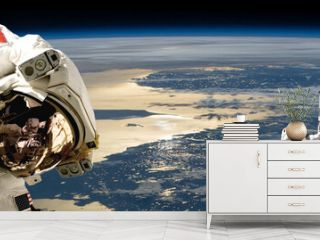 A team of astronauts performing work on a space station.- Elements of this image furnished by NASA.
