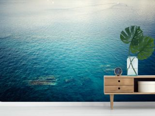 aerial view of clear ocean water, calm waves on a sunny day. Concept tranquill background