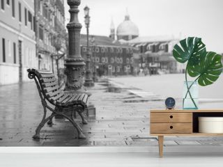 long time exposure of typical wooden bench on promenade in Venice (Venezia) on a rainy day in autumn without people, Italy, Europe, black and white