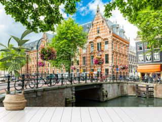 Typical canal side cityscape of Amsterdam, opposite from the 17th century HQ of the Dutch East India Company, now used by the University of Amsterdam
