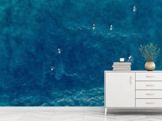 Aerial view of Surfer swimming on board near huge blue ocean wave