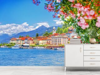 Italy, Europe. Lake Como and lovely village Bellagio, view through pink flowers of oleander plant. Gorgeous travel background of traditional italian small towns, lake Como is popular summer resort.