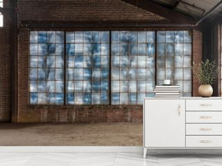Large blue frosted windows in a loft like space of an abandoned factory with brick walls