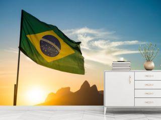 Brazilian flag waving backlit in front of the golden sunset mountain skyline at Ipanema Beach in Rio de Janeiro, Brazil