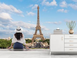 Young traveler woman in white hat looking at Eiffel tower, famous landmark and travel destination in Paris