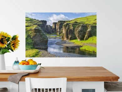 green hills of canyon with river and sky in Iceland
